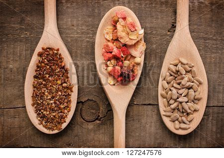 Three wooden spoon with muesli and flax seed and sunflower seed