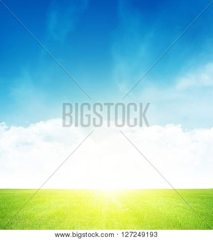 Green grass field and blue sky with clouds on horizon background