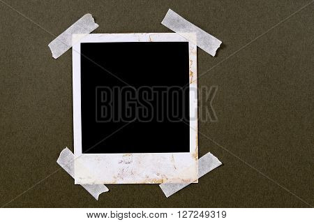 Old vintage stained blank photo print frame taped to brown paper background