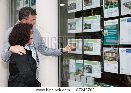 Side View Of A  Couple Looking At Window Display At Real Estate Office