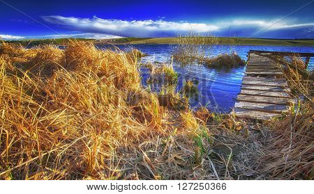 dock on the lake at sunset. Dramatic blue sky. Dry reed