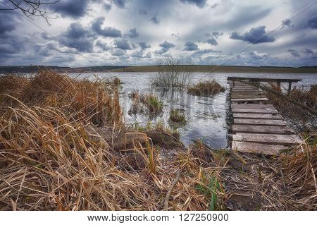 Old wooden pier with dry reed. Cloudy weather
