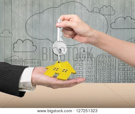 Woman hand giving silver key with gold house shape keyring to man hand on doodles wooden wall background, 3D illustration.