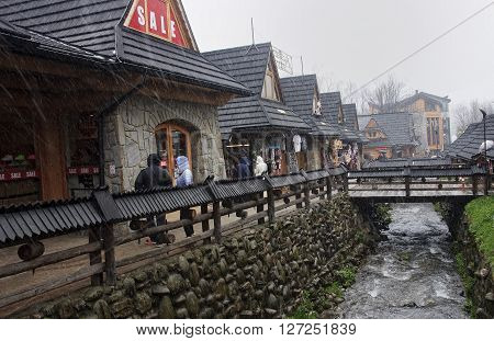 ZAKOPANE POLAND - APRIL 24 2016: Tourists visiting Krupowki street on 24 April 2016 in Zakopane Poland. Krupowki Street is the most popular pedestrian street in Zakopane