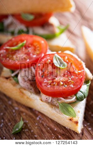 Grilled chicken sandwich with basil, shredded cheese and tomatoes