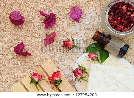 Herbal bath blend spa. Essential oil, salt, soap bar, flower petals scattered on terry towel.