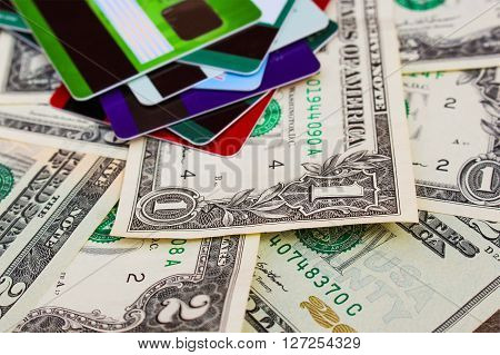 Credit card and dollars on wooden background.