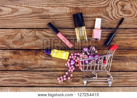 Shopping cart with cosmetics, beads on the old wood background. Toned image.