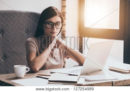 Modern businesswoman. Young beautiful woman in eyewear keeping arms clasped and looking at camera while sitting in chair at her working place