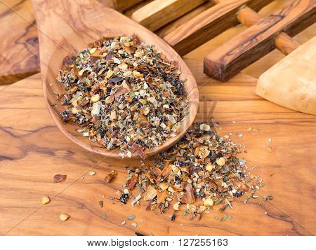 Herbal seasoning in the wooden spoon on the olive wood cutting board