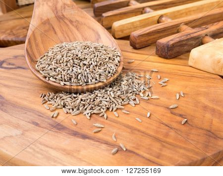 Cumin seeds in the wooden spoon on the olive wood cutting board