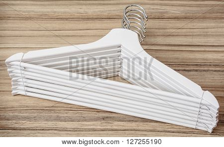 Set of white coat hangers on the wooden background. Home related.