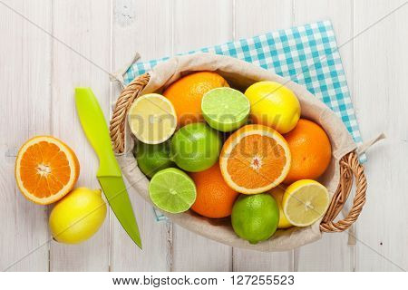 Citrus fruits in basket. Oranges, limes and lemons. Over white wood table background