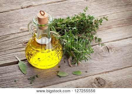 Olive oil and fresh garden herbs on wooden table