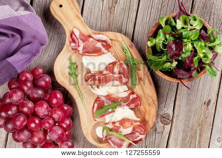 Prosciutto and mozzarella on cutting board over wooden table. Top view
