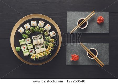 Japanese food restaurant, sushi maki gunkan roll plate or platter set. Set for two with chopsticks, ginger, soy, wasabi. Sushi at rustic wood background and black stone. Top view at black
