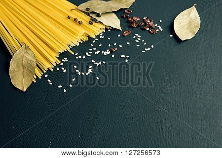 Raw spaghetti and Bay leaf, barberry, pepper, sesame seeds on black-blue wooden background, top view place for text