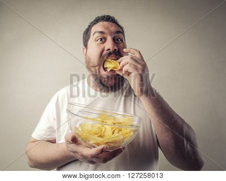 Fat man eating potato chips