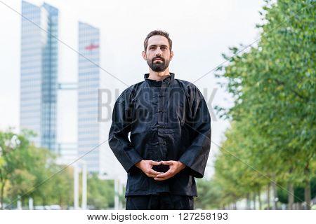 Man meditating doing martial arts in city