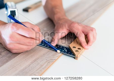 Carpenter marking cut on parquet piece