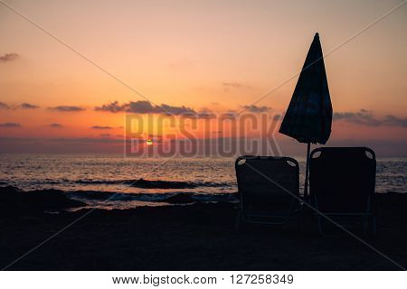 Sunbeds and umbrella standing on the seashore during sunset