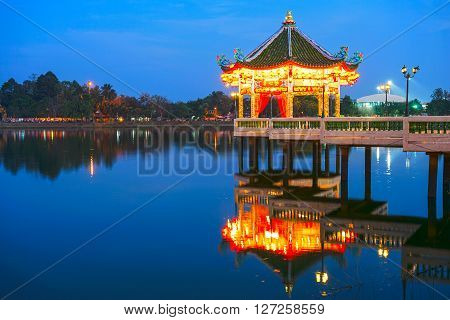 Chinese Pavilion at night architectue with reflection on lake ** Note: Visible grain at 100%, best at smaller sizes