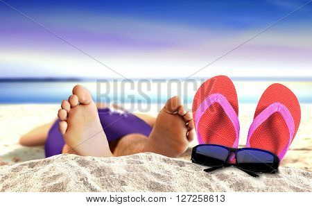 Laying on beach with slipper and sunglasses