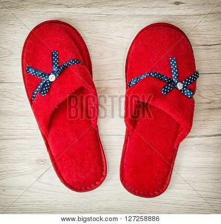 Red slippers with blue ribbon on the wooden background. Beauty and fashion. Retro style. Indoor slippers.