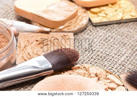 Close-up of flat makeup brush with various products to even out skin tone and create the perfect complexion on sackcloth. Shallow depth of field. Copy space