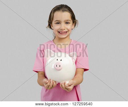 Cute little girl holding a piggybank with her savings