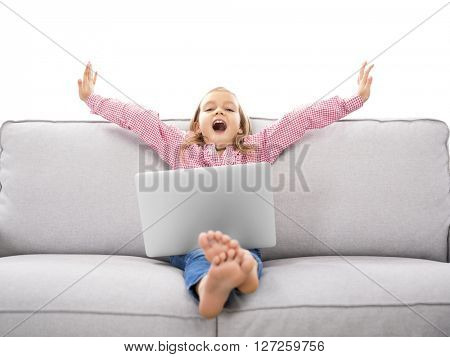 Happy little girl sitting on a couch and working a laptop