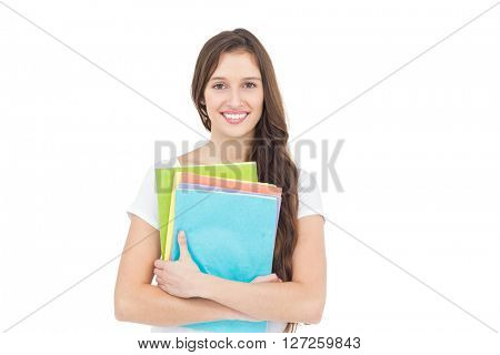 Portrait of smiling female college student holding books while standing on white background