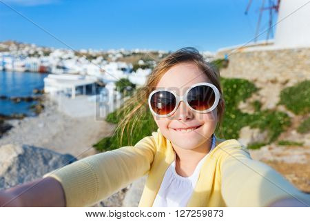 Cute little girl making selfie at Little Venice popular tourist area on Mykonos island, Greece