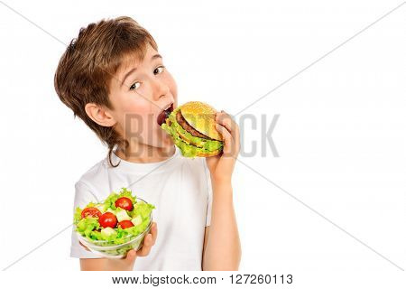 A nine year old boy making choice between fast food burger and fresh vegetable salad. Fast food. Concept of healthy and unhealthy food. Isolated over white.