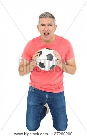 Man shouting and holding a soccer ball on white background