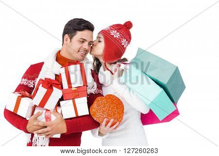 Happy couple with winter clothes holding gift boxes and shopping bags on white background