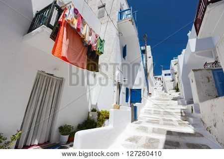 Typical street of greek traditional village with white walls and colorful doors, windows and balconies on Mykonos Island, Greece, Europe