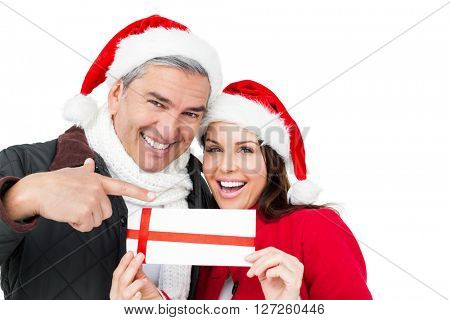 Festive couple pointing christmas gift on white screen