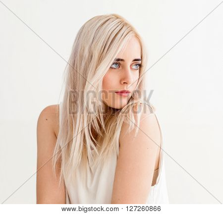 Woman with nude makeup on white background. Blonde calm girl isolated on white. Fashion portrait of young beautiful girl in light studio.