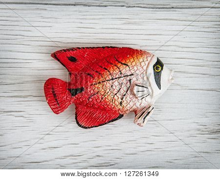 Humorous red plastic fish toy on the wooden background. Symbolic object. Sea life.