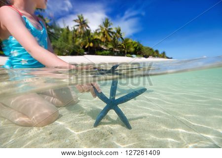 Split underwater photo of a little girl playing with blue starfish on shallow clear ocean water