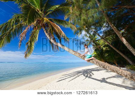 Cute boy at tropical beach sitting on palm tree during summer vacation