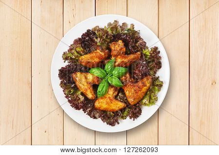 American cuisine, restaurant food -  fried roasted chicken wings on lettuce with basil at round white plate at wooden background. Top view, flat lay