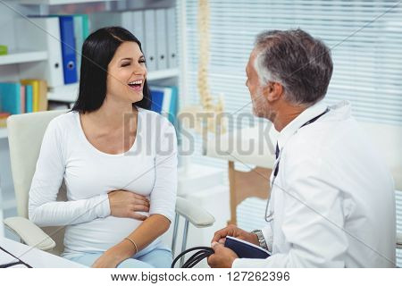 Pregnant woman talking to doctor in clinic