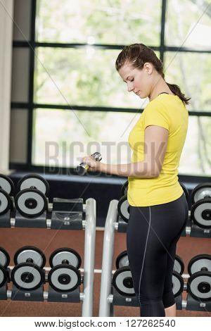 Brunette lifting dumbbell at gym