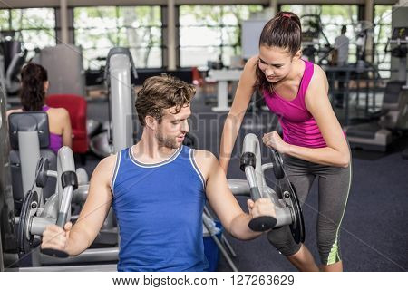 Trainer woman helping athletic man in gym