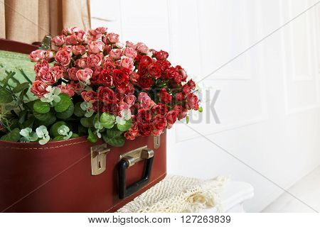 Unusual wedding floral decor composition - flowers in vintage brown suitcase. Old suitcase with rose flowers. Bouquet of rose flowers. Vintage, rustic, country decor. Floristic decoration. Flowerbed.