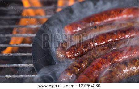 Grilling sausages on barbecue grill, close-up.