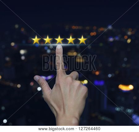 Hand click on five yellow stars to increase rating over blurred light city tower background Feedback concept