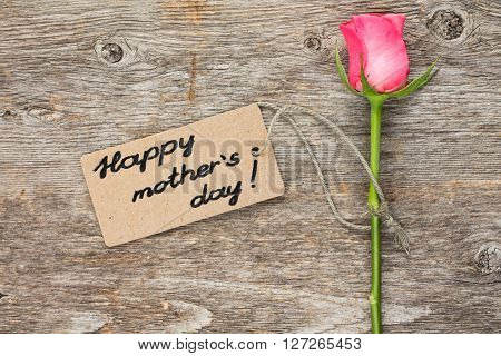Mothers day card with pink rose on wooden board.